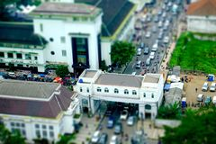 Crowded road traffic seen from top. With many motorcycles and car in the street, and big pedestrian bridge, tilt shift miniature Royalty Free Stock Images
