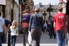 Crowded shopping street. Crowds of shoppers on a busy high street - taken with slow shutter speed to blur people stock photo
