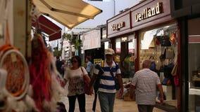 Crowded shopping street near the Aegean sea promenade. stock video