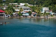 Crowded Shoreline. A small piece of the shoreline with homes and buildings crowding the sandy beach at the port in Roatan, Honduras Stock Image