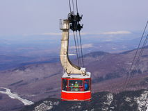 Crowded ski gondola and snow mountains background. The ski gondola claiming up to the peak of the mountain in the Northeast of USA. In the background are snowy Stock Image
