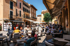 Crowded square of Alcudia. People relax at an outdoor cafe. ALCUDIA, MAJORCA, SPAIN - May 23, 2015. Crowded square of Alcudia. People relax and enjoy their Stock Image