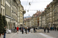 Crowded street in the old town of Bern. Bern, Switzerland - April 17, 2017: Crowded street in the old town. In the middle of the street there is a fountain and Royalty Free Stock Images