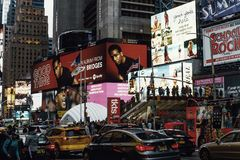 Crowded street in Times Square in New York. Buildings are covered in advertising panels and morning rush is in a full swing stock image