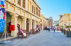 Crowded streets of Souq Waqif, Doha, Qatar. DOHA, QATAR - FEBRUARY 13, 2018: The crowded street of Souq Waqif, people relax on the benches, visit local cafes and Stock Photography