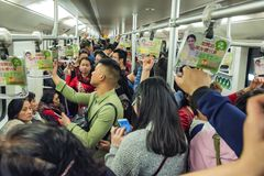 Crowded subway train carriage, Shanghai China. Hundreds of people cram into a subway train carriage on their way home from work during the late afternoon in stock images