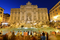 Crowded Trevi fountain (Fontana di Trevi) at night, Rome, Italy Stock Photos