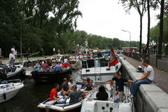 Crowded water lock in Amsterdam. Lots of boats full of people waiting in the water lock to pass to the other side of the canal during Sail Amsterdam Royalty Free Stock Images