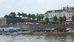 Crowded waterside in Cascais Portugal with rippling sea, buildings at background. Stock footage stock footage
