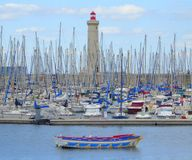 Many yachts in harbour and lighthouse. The crowded yacht harbour and lighthouse in the port of Sete in France royalty free stock photo