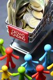 Crowdfunding concept with multicolored figurine and shopping trolley full of money on dark background royalty free stock photos