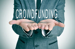 Crowdfunding. Man wearing a suit holding the word crowdfunding in his hands Stock Image