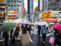 Crowds at Crossing in Japan. Crowds of Japanese Shoppers with iconic clear umbrellas crossing a street in Japan full of neon signs royalty free stock image