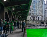 Crowds of families and partiers gather to celebrate St. Patrick`s Day. Over a dyed green Chicago River stock photo