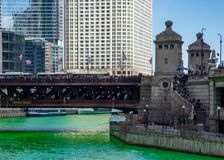 Crowds gather on Michigan Avenue and on stairs leading to riverwalk, which is blocked off by security. On St. Patrick`s day with dyed green Chicago River royalty free stock photo