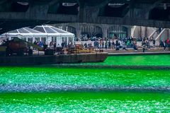Crowds gather on riverwalk winery to celebrate St. Patrick`s Day. Along a dyed green Chicago River royalty free stock image