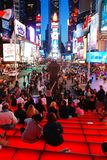 The steps of TKTS in Times Square. Crowds gather on the steps of TKTS in Times Square as the lights begin to take effect royalty free stock photos