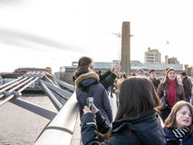 Crowds on Millennium Bridge, with couple taking selfie in the foreground, London, UK Stock Photos