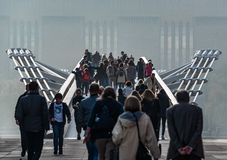 Crowds on Millennium Bridge, London. A foggy day in London as crowds of people cross the river Thames over the Millennium Bridge towards the Tate Modern art stock photos