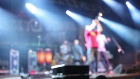 Crowds at open air rock festival. Defocused zoomed shot of band member playing on the stage stock video footage