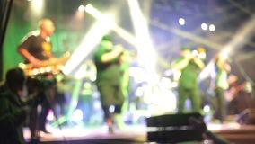 Crowds at open air rock festival. Slightly defocused close-up of band performing on the stage stock footage