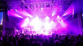 Crowds at open air rock festival. Wide angle front view of band perfoming on the stage stock footage