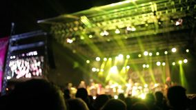 Crowds at open air rock festival. Wide angle side view of stage with band performing on it stock video