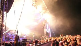 Crowds at open air rock festival. Wide angled side view with panning on the crowds stock footage