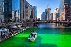 Crowds and party boats enjoy festivies around a dyed green Chicago River stock image