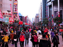 Crowds in a pedestrian street. Nanjing Road Pedestrian Street, Shanghais most bustling commercial street. Crowds in a pedestrian street, in shanghai. Taken in Stock Photo