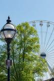 Very obvious big wheel sign on lamp post. Crowds of people crossing footbridge to get to big ferris wheel Stock Images