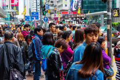 Crowds of people crossing King`s Road in Hong Kong Stock Photos