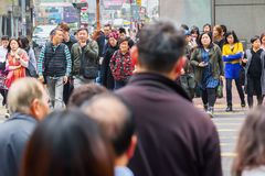 Crowds of people crossing a road in Hong Kong royalty free stock photo