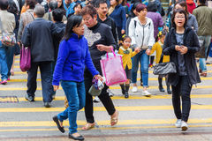 Crowds of people crossing a street in Hong Kong stock photo