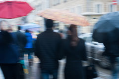 Crowds of people crossing street on rainy day in the city Stock Photos