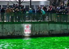 Crowds of people gather along the Chicago River, which is dyed green for St. Patrick`s day. Crowds of people gather along the Chicago River, which is dyed green Stock Photo