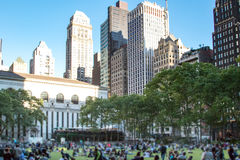 Crowds of people gather on the grass at Bryant Park for a summer. Festival in Midtown Manhattan in New York City Stock Image