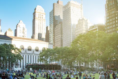 Crowds of people gather on the grass at Bryant Park for a summer. Festival in Midtown Manhattan in New York City Royalty Free Stock Photos