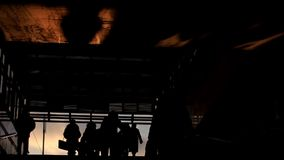 Crowds of people get out from subway at winter sunset, silhouette stock footage