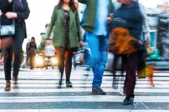 Crowds of people in motion blur crossing a city street Royalty Free Stock Photography