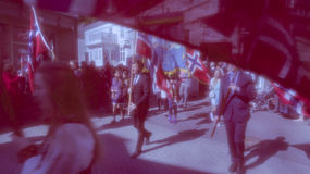 Crowds of people during the parade obscured by the Norwegian fla Stock Photography