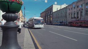 Crowds of people walk on avenue in summer sunny day in city. Trolleybus on road. Slow motion stock video footage
