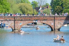 Crowds of people walkingt across arched bridge with multiple small boats passing underneath. Stratford upon Avon Warwickshire England UK May 6th 2018 bank royalty free stock photography