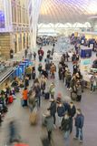 Crowds Of Rail Commuters. Crowds of commuters sit while others come and go at Kings cross station, london, england, uk Stock Photo