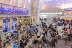 Crowds Of Rail Commuters. Crowds of commuters sit while others come and go at Kings cross station, london, england, uk stock photography