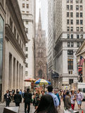 Crowds stroll Wall Street; Trinity Church visible at end. Stock Photo