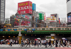 Crowds, Train and a Billboard in Tokyo. A train speeds past as crowds cross beneath, holding umbrellas aloft. Japanese billboards are in the background Stock Photography
