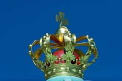 Crown. A golden crown with a cross on top against a clear blue sky Royalty Free Stock Image
