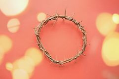 Crown of Jesus with Blood Droplets. Crown of thorns like Jesus Christ wore with drops of blood on tips of thorns with bokeh lights over coral background. Perfect stock photography