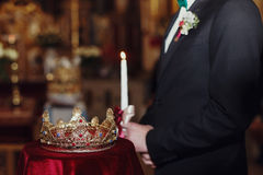 Crown lies on the red velvet while bridegroom stands on the back Royalty Free Stock Photography